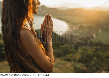 Woman Praying Alone At Sunrise. Nature Background. Spiritual And Emotional Concept. Sensitivity To N