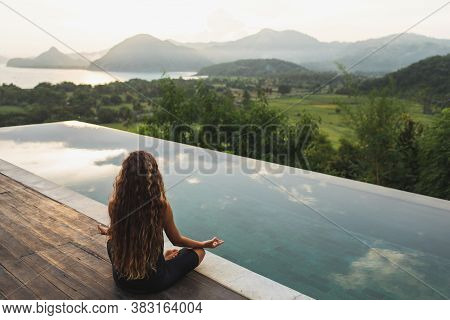 Woman Meditating And Practicing Yoga Alone At Sunrise Near Infinity Pool With Mountains On Horizon.