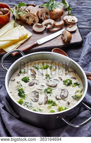Mushroom Cheese Broccoli Soup In A Pot With Ingredients At The Background, Vertical View From Above,