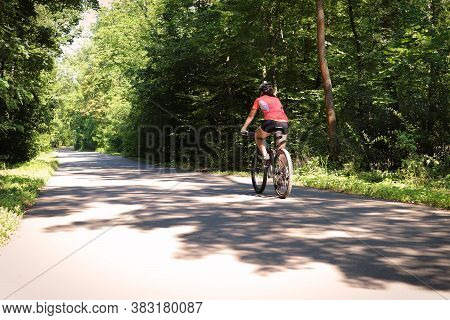 Cyclist Rides A Mountain Bike On The Road Through The Woods.