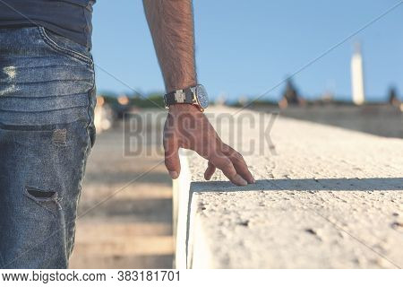 Young Man Puts His Hand On A Stone