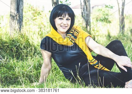 Woman In Black Clothes Is Sitting On The Grass Field And Relaxing View