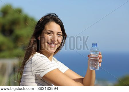 Happy Woman Holding A Bottle Of Water Looks At You In A Balcony On The Beach