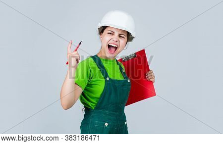 Express Dissatisfaction. Angry Girl In Helmet With Folder On Building Site. Builder In Helmet In Fro