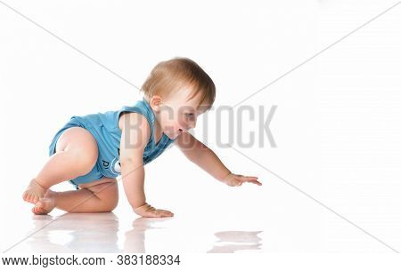Little Toddler Boy In Blue Bodysuit Tries To Crawl On A White Background