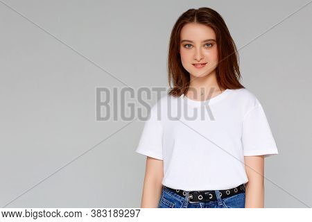 Close Up Portrait Of Smiling Young Woman In White T-shirt Looking At Camera, Isolated On Gray Backgr