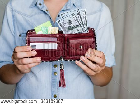 A Dark Red Wallet With Cash Dollars And Credit Cards Is Held By A Young Man. Cash And Non-cash Money