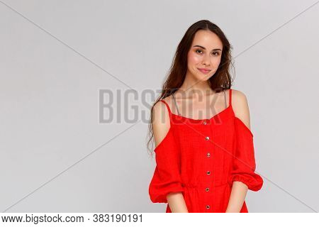 Close Up Portrait Of Smiling Young Woman In Red Dress Looking At Camera, Isolated On Gray Background
