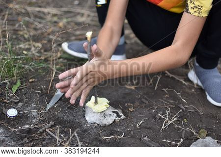 Child Boy Makes Fire By Friction Method. Survival Skills In The Forest. Children's Tourist Rest In T
