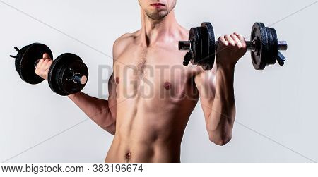 Man Holding Dumbbell In Hand. Skinny Guy Hold Dumbbells Up In Hands. A Thin Guy In Sports With Dumbb