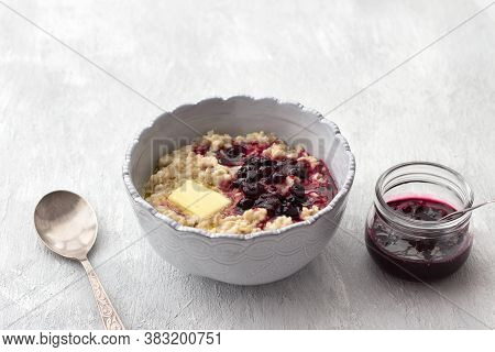 Delicious Oatmeal Porridge With Butter And Jam In A Gray Bowl On A Light Gray Background. Healthy Ho
