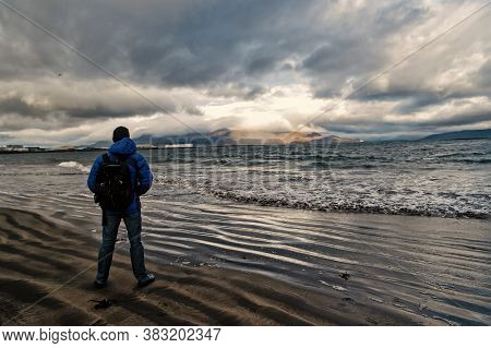 Man Looks On Horizon With Reykjavik Seascape In Iceland. Future Goals Concept. Nature Lovers. Travel