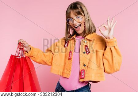 Woman With Price Tags On Jacket Holing Red Shopping Bags And Showing Okay Gesture On Pink Background