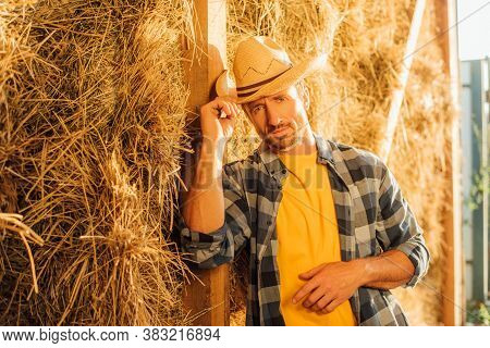 Rancher In Plaid Shirt Looking At Camera And Touching Straw Hat While Leaning On Hay Stack