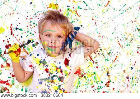 Happy Cute Dirty Boy Child Playing With Paint And Brush On Colorful Background. Drawing Concept.