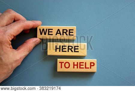 Wooden Blocks With Text 'we Are Here To Help'. Male Hand. Beautiful Blue Background, Copy Space. Bus