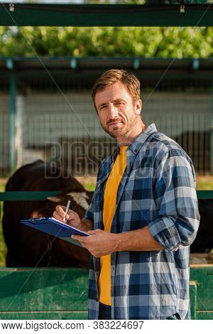 Rancher In Checkered Shirt Writing On Clipboard While Standing Near Cowshed And Looking At Camera