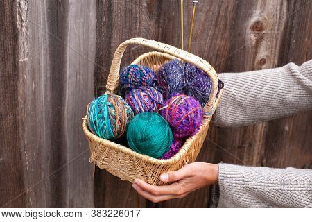 Wicker Basket With Colorful Bright Balls Of Wool Yarn For Knitting In Female Hands. Knitting Yarn, N