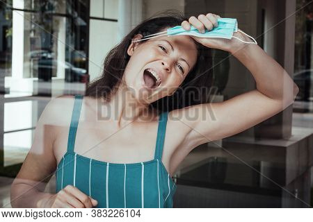Woman Tired Of Isolation And The Pandemic Takes Off Her Medical Mask From Her Face In Protest And Di