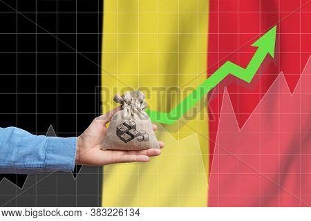 The Concept Of Economic Growth In Kingdom Of Belgium. Hand Holds A Bag With Money And An Upward Arro