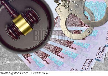 50 Ukrainian Hryvnias Bills And Judge Hammer With Police Handcuffs On Court Desk. Concept Of Judicia