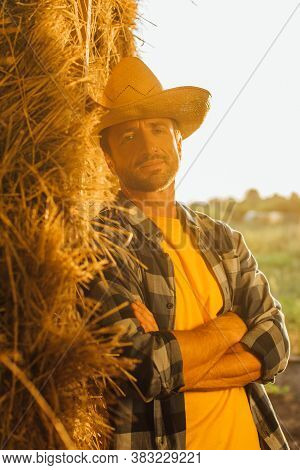 Rancher In Checkered Shirt And Straw Hat Looking At Camera While Leaning On Bale Of Hay With Crossed