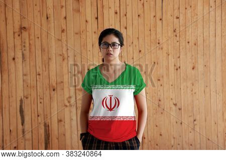 Woman Wearing Iran Flag Color Shirt And Standing With Two Hands In Pant Pockets On The Wooden Wall B