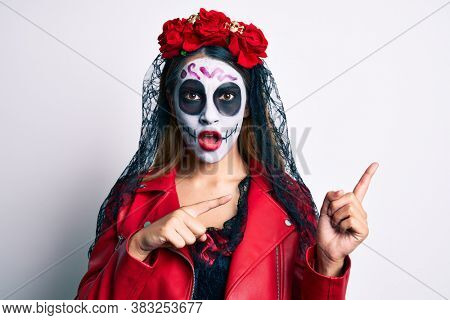 Woman wearing day of the dead costume pointing with fingers to the side in shock face, looking skeptical and sarcastic, surprised with open mouth