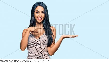 Beautiful hispanic woman wearing summer dress amazed and smiling to the camera while presenting with hand and pointing with finger.