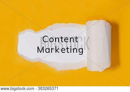 The Text Content Marketing Appearing Behind Torn Yellow Paper