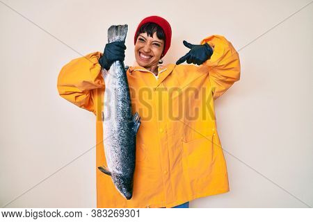 Beautiful brunettte fisher woman wearing raincoat holding fresh salmon smiling happy pointing with hand and finger