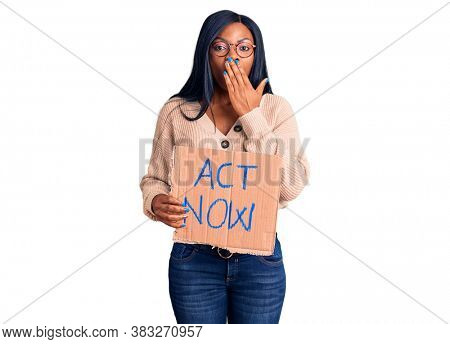 Young african american woman holding act now banner covering mouth with hand, shocked and afraid for mistake. surprised expression