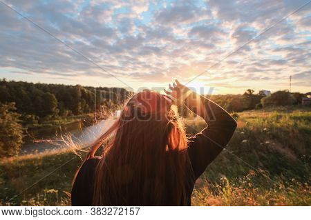 Young Adult Woman Standing Alone And Staring At Orange Yellow Sunset Over River. Girls Silhouette Cl
