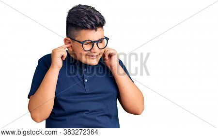 Little boy kid wearing casual clothes and glasses covering ears with fingers with annoyed expression for the noise of loud music. deaf concept.