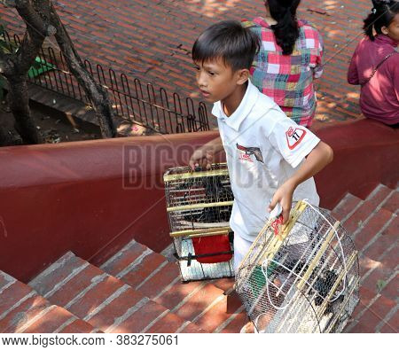 Phnom Penh, Cambodia, Feb 4, 2019 : The Boy Holds The Bird Cage For Sale To Philanthropist To Buy A