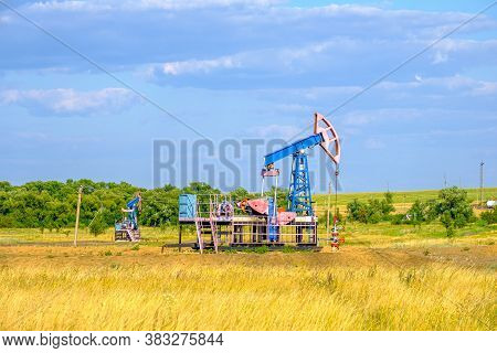 Rocking Chair For Oil Extraction In The Arid Steppe On A Sunny Day Against The Blue Sky. Industrial