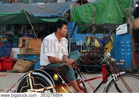 Yangon, Myanmar Feb 21, 2019:myanmarese Man Sitting On His Bicycle Tricycle Taxi For Waiting Passeng