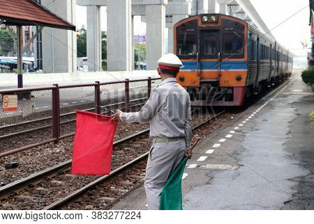 Train Officer Is Acting To Signal Safety Precautions For Passengers And People While The Train Is La