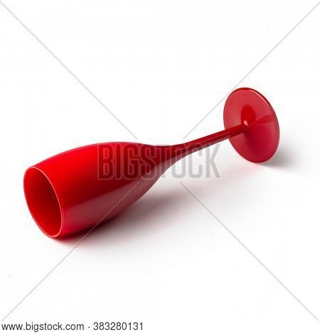 Isolated overturned red champagne glass on white background for festive events