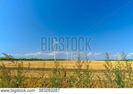 Wind Turbines On A Sunny Summer Day Against A Blue Cloudless Sky. An Alternative Way To Get Electric
