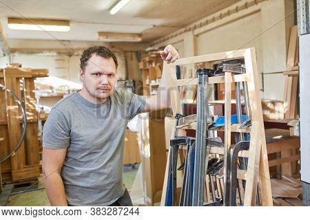 Young craftsman as a Carpenter with a selection of clamps