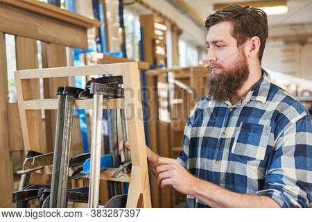 Hipster man with a beard as a carpenter or furniture maker works with clamps
