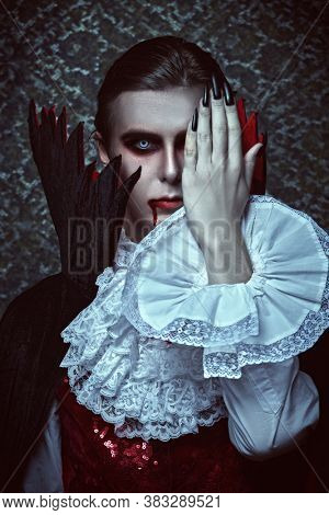 Portrait of a traditional vampire aristocrat of the 19th century in an elegant suit and with a drop of blood on his lips. Count Dracula. Halloween.