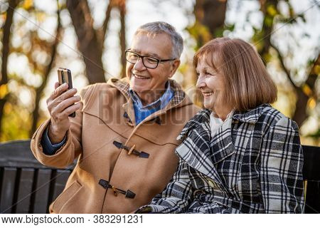 Senior Couple Is Sitting On Bench In Park And Enjoying Autumn.
