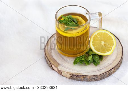 A Cup Of Herbal Tea With Lemon And Mint On A Wooden Tray On A White Background