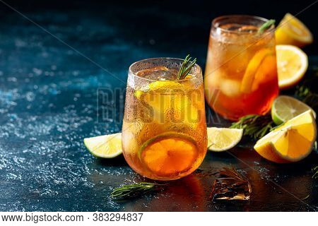 Iced Tea With Lemon, Lime And Ice Garnished With Rosemary. Frozen Glasses With Citrus Slices On A Da
