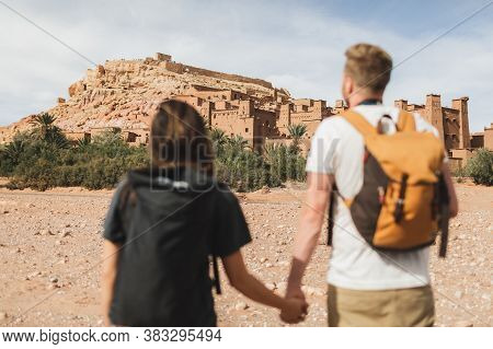 Couple Of Backpacker Travelers On Background Ait Ben Haddou Ksar In Ouarzazate. Welcome To Morocco.