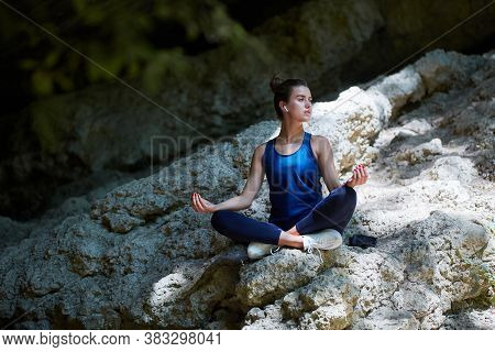 Woman Meditates On Fresh Air At Sharp Hill. Yoga Time, Meditation And Pilates Concept. Lady Wearing