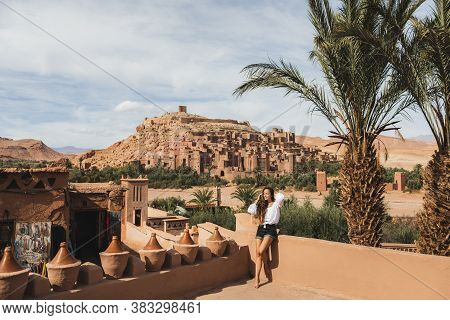 Beautiful Young Woman Happy To Travel In Morocco. Ait-ben-haddou Kasbah On Background. Wearing In Wh