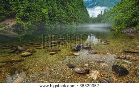 Clear Lake With Rocks And Mist In Distance